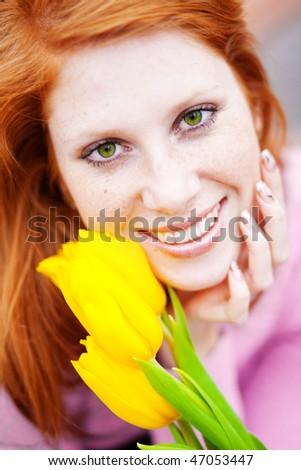 Close-up face of beautiful smiling girl with spring flowers - stock photo