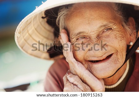 Close up face of beautiful smiling woman with wrinkles. Elderly senior. - stock photo