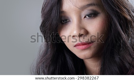Close up face of young Asian woman looking down with melancholic expression, on grey background - stock photo