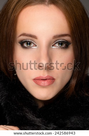 Close up face portrait of a serene young brunette woman wearing elegant makeup in a winter scarf looking directly at the camera with a serious enigmatic expression - stock photo