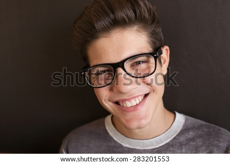 Close up face portrait of an attractive teenager boy smiling at the camera wearing reading glasses spectacles at home, interior. Student lifestyle. Eyes, vision, sight. Sensory perception, indoors. - stock photo