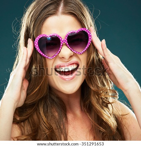 Close up face portrait of emotional woman open mouthed wearing heart sunglasses. Studio portrait of female model. - stock photo