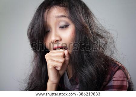 Close up face portrait of sleepy Asian girl yawning, over grey background - stock photo