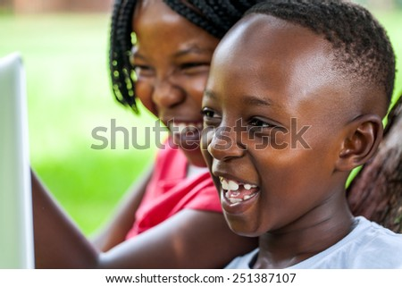 Close up face shot of African kids laughing at movie scene on digital tablet outdoors. - stock photo