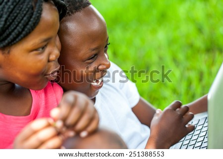 Close up face shot of African kids laughing at scene on laptop outdoors. - stock photo