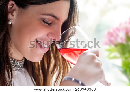 Close up face shot of attractive brunette smelling wine with eyes closed. - stock photo