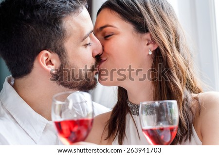 Close up face shot of couple kissing at romantic dinner. Out of focus wine glasses in foreground. - stock photo