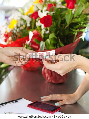 Close up faceless detail of a florist business woman shop attendant taking a cash bill note payment from her client customer during a sunny day. Working business outdoors. - stock photo