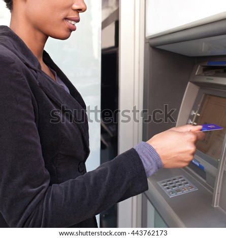 Close up faceless portrait of beautiful elegant african american business woman holding a credit card in bank cash point in city, outdoors lifestyle. Professional ethnic woman accessing funds in bank. - stock photo