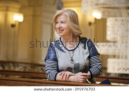 Close up facial portrait of a beautiful senior woman looking at the camera with a warm friendly smile and attentive expression - stock photo