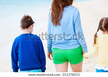 Close up family of mother and kids on tropical vacation walking along the beach - stock photo