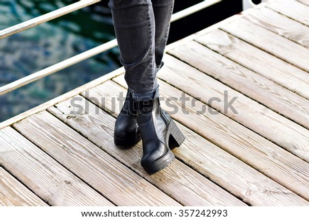 Close up fashion image of retro brutal boots, woman posing at wooden floor near sea, street style, total black, hipster look. - stock photo