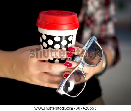 Close up fashion image of woman holding cup of her morning cappuccino, wearing red stylish shirt, and hipster grey sunglasses.Young woman drinking coffee from disposable cup.Woman holds red cup  - stock photo