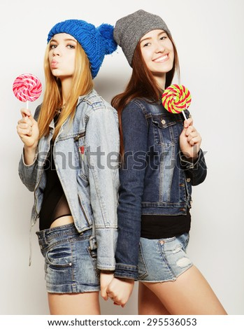 Close up fashion lifestyle portrait of two young hipster girls best friends, holding candys, making funny faces and have good time. - stock photo