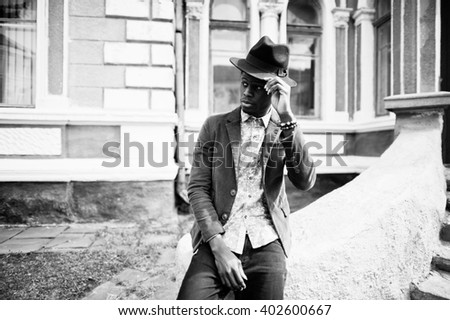 Close up fashion portrait of black african american man on green velvet jacket and black hat sit on stairs background old mansion. B&W photo - stock photo