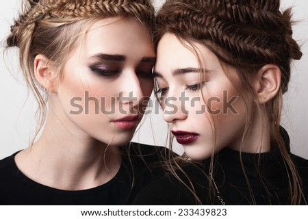 Close-up fashion portrait of couple beauty girls with pigtails - stock photo