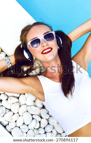 Close up fashion portrait of cute smiling young girl, listening and enjoy music on headphones, laying on her vacation her pool, wearing ponytails sunglasses and bright make up. - stock photo