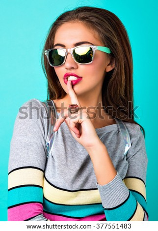 Close up fashion portrait of elegant pretty woman, sexy face bright make up, stylish casual sweater, spring pastel colors, put finger to her mouth. - stock photo