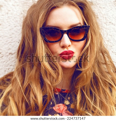 Close up fashion portrait of pretty girl, having fun and making funny faces, have long amazing curled hairs, wearing vintage sunglasses, and bright lipstick. - stock photo