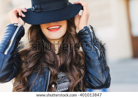Close up fashion portrait of pretty seductive young woman with  wool hat  smiling, laughing ,  posing outdoor. Red lips, wavy hairstyle.  - stock photo