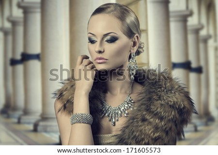 close-up fashion portrait of sensual blonde girl with luxury style, posing with elegant hair-style and make-up and wearing fur shawl and rich shiny jewellery. Aristocratic expression  - stock photo