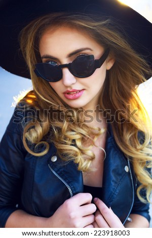 Close up fashion portrait of sexy young sensual stylish woman, with long curled blonde hairs wearing stylish vintage hat,cat eye sunglasses, and trendy leather jacket. - stock photo
