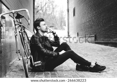 Close up fashion portrait of stylish handsome hipster guy sitting at city park near his fixed bike - stock photo