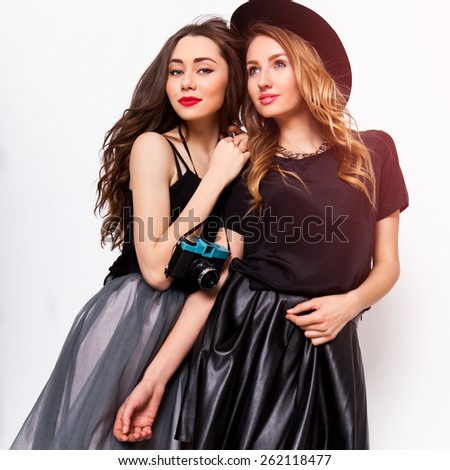 Close up fashion portrait of two elegant stylish  women wearing a leather  skirt and black hat , holding  retro camera.  Posing against white background. - stock photo