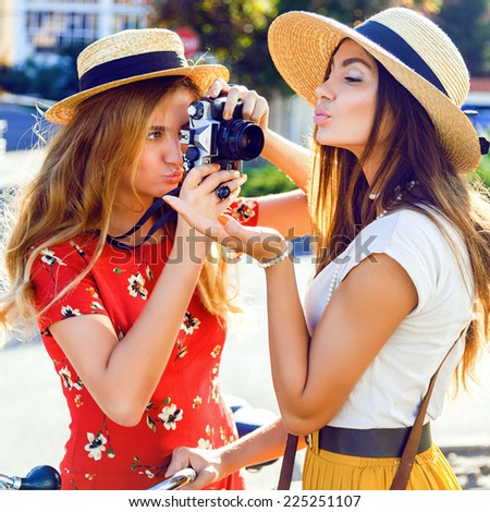 Close up fashion portrait of two funny young pretty blonde and brunette sisters, making funny pictures on retro vintage camera, two stylish best friends having fun together. - stock photo