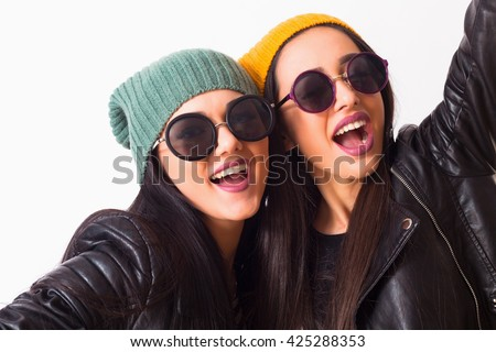 Close up fashion portrait of two teenage hipster friends girls Studio portrait of two cheerful best friends sisters having fun,screaming,laughing,happy together.Wearing hats and trendy sunglasses. - stock photo