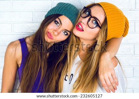 Close up fashion portrait of two young pretty hipster girls wearing bright make up hats and glasses. Studio portrait of two cheerful best friends sisters having fun and making funny faces. - stock photo