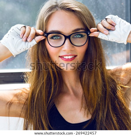 Close up fashion  portrait of young sexy stunning sensual woman with long brunette hairs perfect skin and bright make up, wearing clear hipster vintage glasses. - stock photo