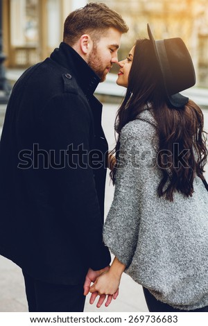Close up fashion portrait  of young  stylish glamour girl and  guy  in love . Couple  walking down the street in  sunny fall . Warm  autumn colors. Wearing black  trendy outfit . - stock photo