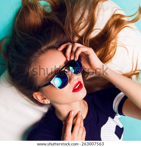 Close up fashion studio portrait of elegant beautiful blond woman with stylish sunglasses wearing sportive hipster outfit . Red lips blue background . - stock photo