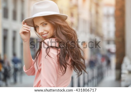 Close-up Fashion woman portrait of young pretty trendy girl posing at the city in Europe,summer street fashion,holding retro fedora hat popular until the 60s.laughing and smiling portrait.trendy - stock photo