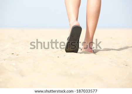 Close up feet in sandals walking on sand at the beach - stock photo