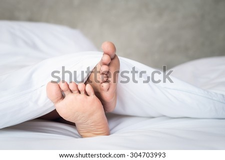 Close up feet of women on white bedding in the morning time - stock photo