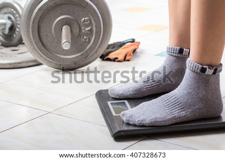 Close up female feet on digital weighting scale. - stock photo