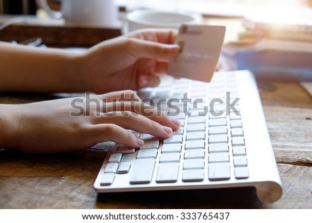 Close up female hands holding credit card using laptop for online shopping concept. - stock photo