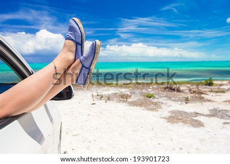Close up female legs from the window of a car  - stock photo