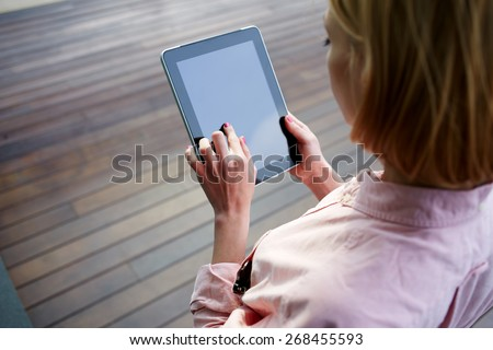 Close up female student hands using blank screen touch pad against wooden background, freelancer woman working on digital tablet with copy space, hipster zooming digital image on touchscreen device - stock photo