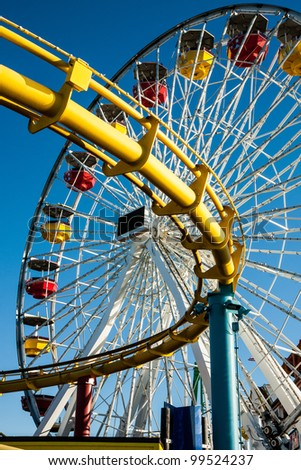 Close up ferris wheel and roller coaster track - stock photo