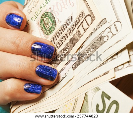 close up fingers with blue creative pattern manicure holding dollars - stock photo