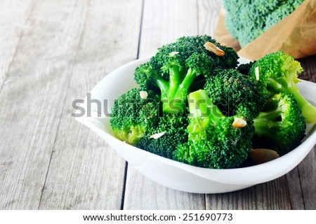 Close up Flavored Steamed Fresh Broccoli on White Plate, Served on Top of Wooden Table. - stock photo