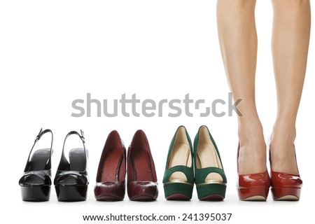 Close up Flawless Woman Legs in Glossy Red High Heel Shoes Standing Between Other Elegant High Heels. Isolated on White Background. - stock photo