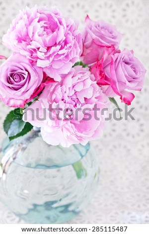 Close-up floral composition with a pink peony and roses on a light background. - stock photo