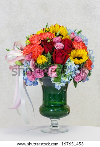 Close up flower bouquet in in glass vase on white table beside grunge concrete wall - stock photo
