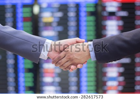 close up focus business man handshake on blurred stock trade board background:investor and broker in suit outstretched arm hand shake togetherness for trust:advisor/consulting investment conceptual. - stock photo