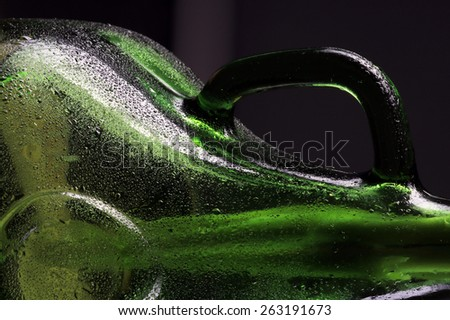 close-up fragment green bottle with a handle covered with dew on a black background studio - stock photo