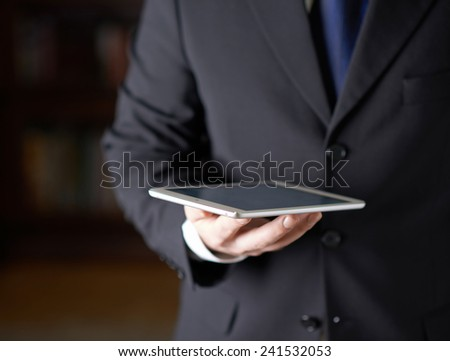 Close-up fragment of a man in a business suit holding a pad tablet in his hands, shallow depth of field composition - stock photo